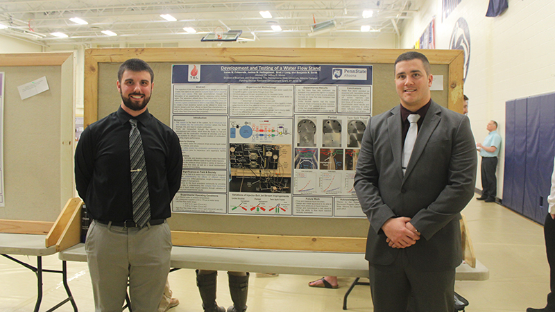Student presenters Matthew Littler and Benjamin Smith pose for a photo in front of their poster presentation.