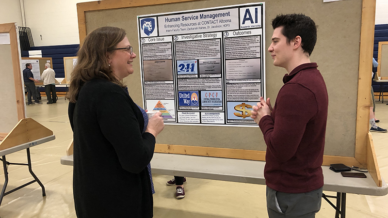 Student presenter Zachariah Haines chats with faculty member Melisaa Koehler