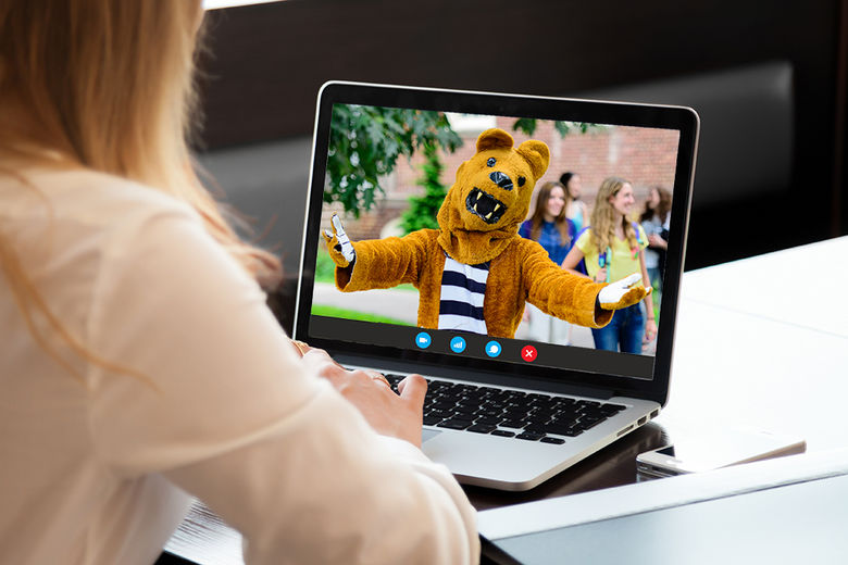Woman chatting with the Nittany Lion on a Laptop