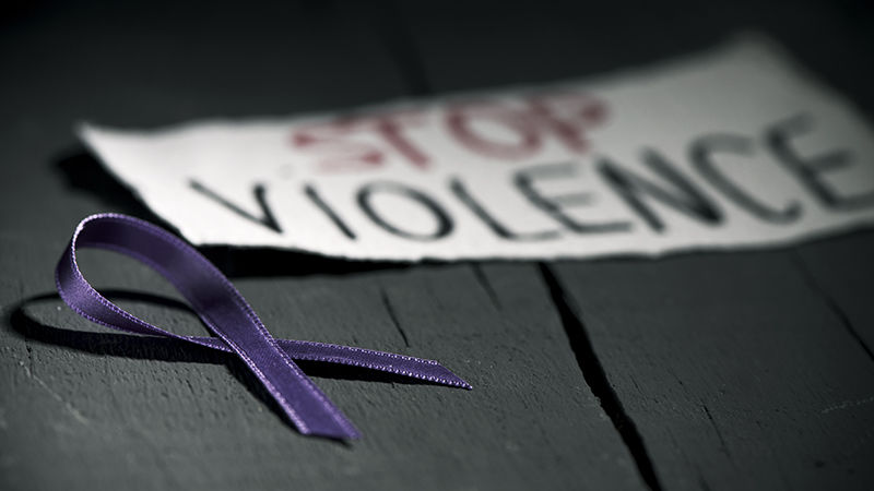 a purple ribbon and a sign reading Stop Violence