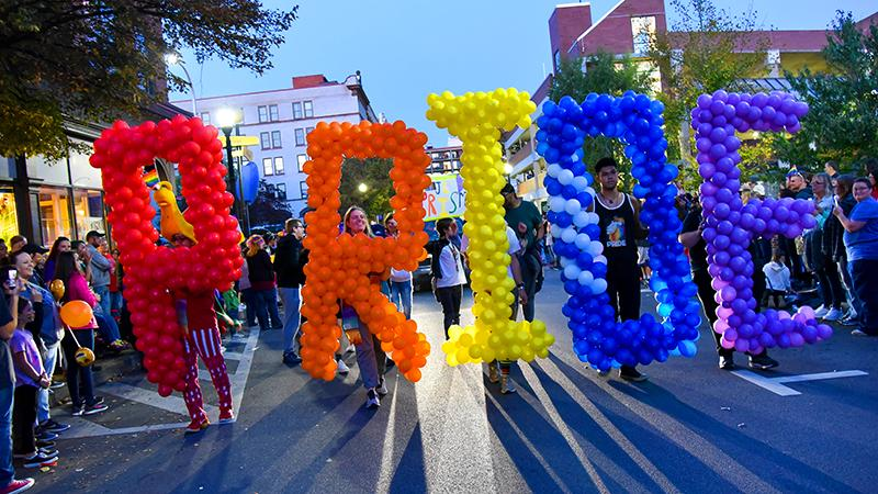 Students hold up balloons spelling Pride at the Penn State Altoona Pride Parade