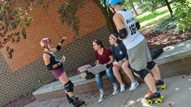 Rebecca Strzelec and Molly Kellom talk to others on campus about roller derby