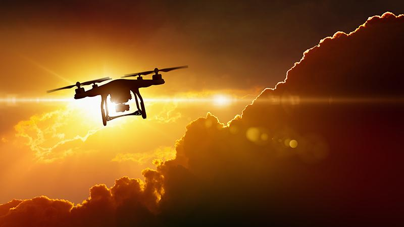 A drone flying away at sunset