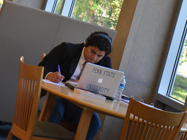 A student wearing a suit studies in the Eiche Library