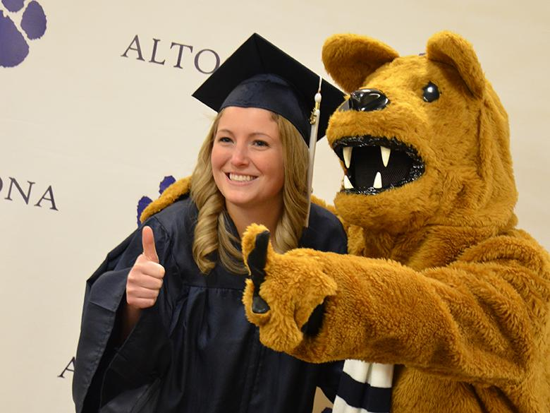 A recent graduate posing with the Nittany Lion