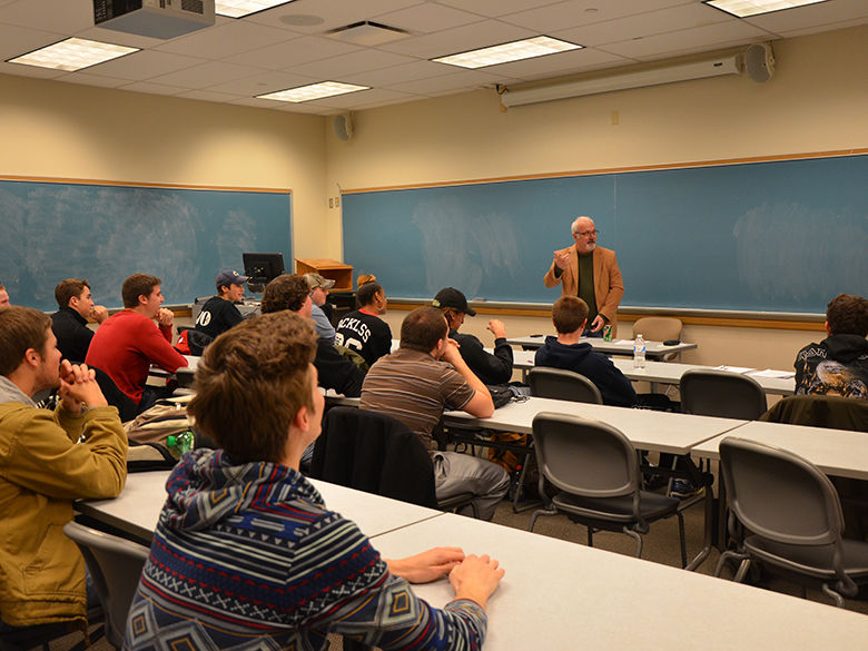 Bill White lecturing in a classroom full of students