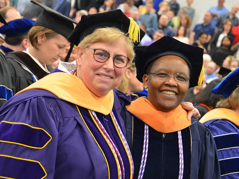 Two nursing professors pose at commencement ceremony