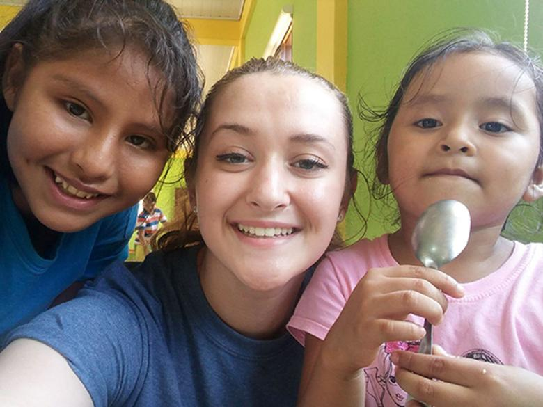 A Penn State Altoona Enactus student with children in Bolivia