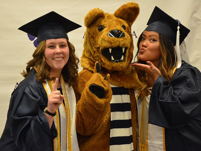 Two recent graduates making kissy faces with the Nittany Lion