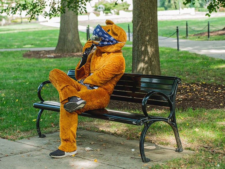 The Nittany Lion mascot sitting on a bench wearing a mask
