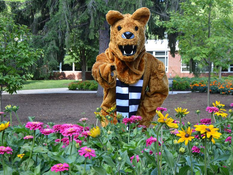 The Nittany Lion posing behind a clump of flowers