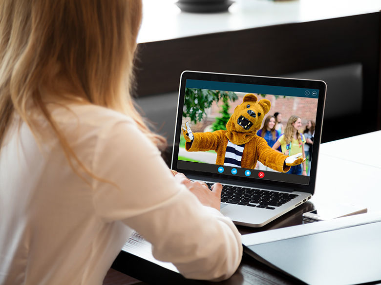 A young woman chatting with the Nittany Lion mascot on a laptop