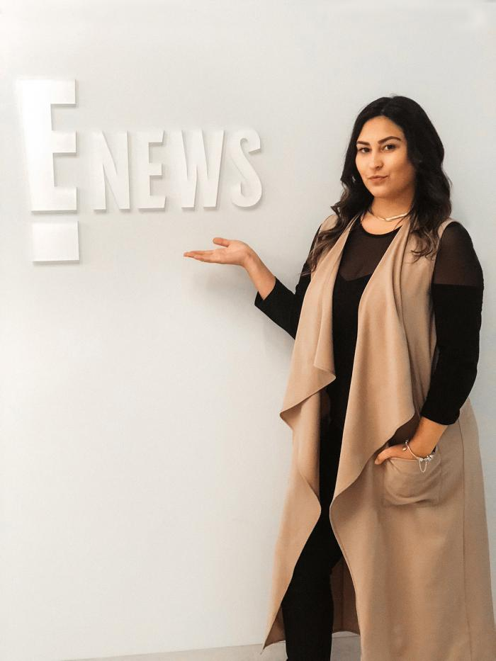 Catherine Rivera Chardon poses by the E! News logo during her internship