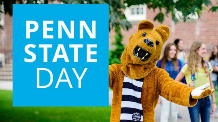 Nittany Lion hodling a Penn State Day sign