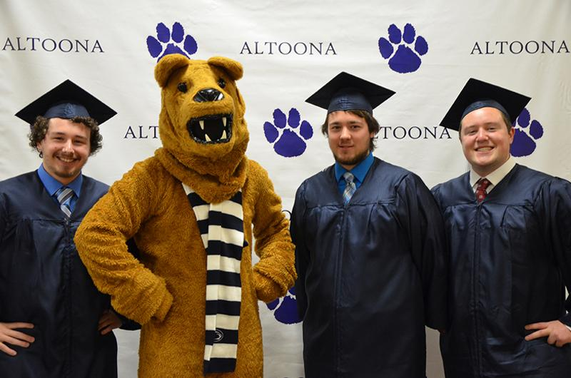 Graduates pose with the Nittany Lion at Fall 2016 Commencement