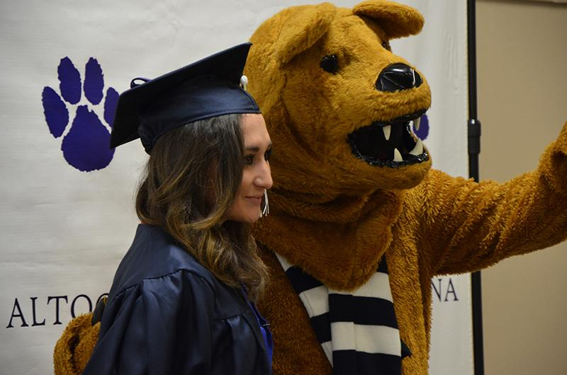 A Graduate poses with the Nittany Lion at Fall 2016 Commencement