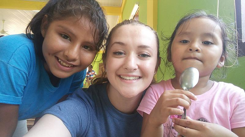 Kelsey Brumbaugh poses with two girls at Andrea's Home of Hope and Joy in the cafeteria