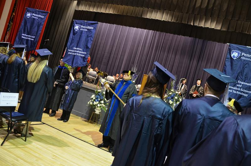College Marshal Bill Engelbret (center) looks on as graduates, faculty, and staff process.