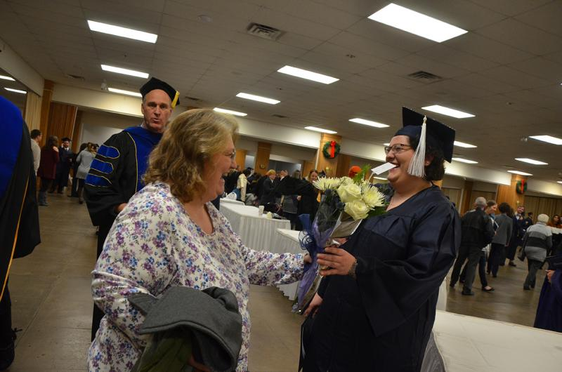 A proud family member presents flowers to a graduate at the Fall 2017 Commencement ceremony