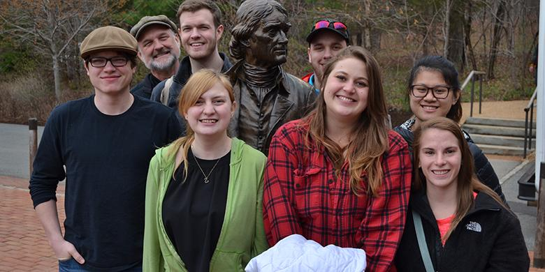 History students and faculty posing with a statue