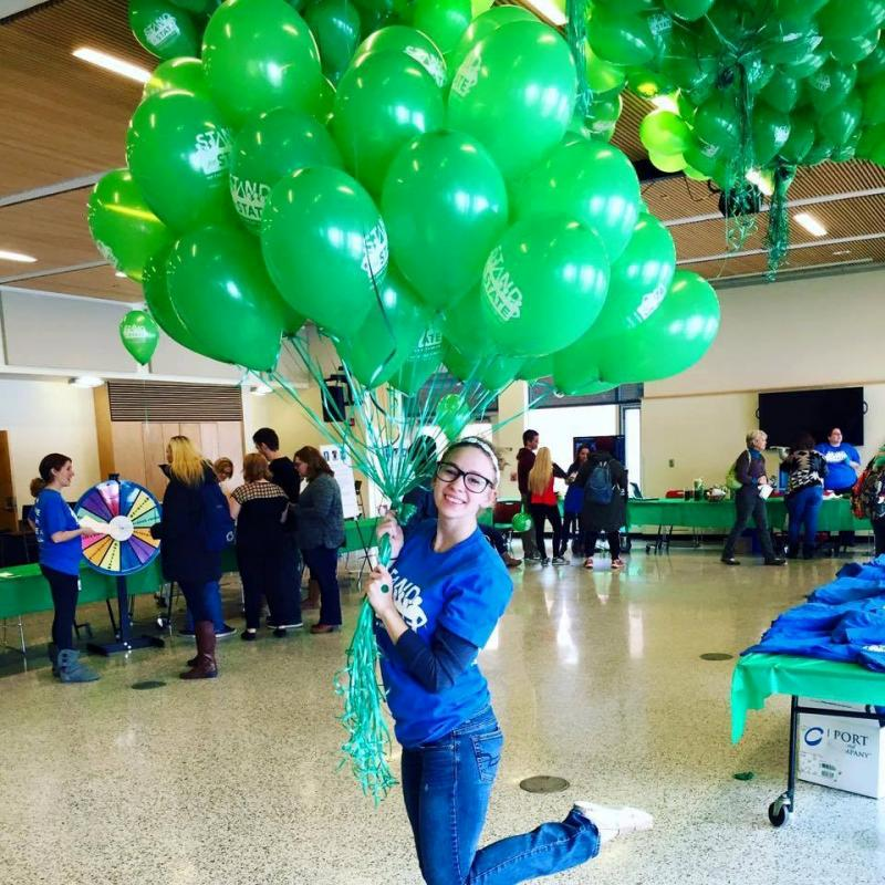 Gabrielle Davidson poses with a cluster of balloons at a Stand for State bystander intervention event.