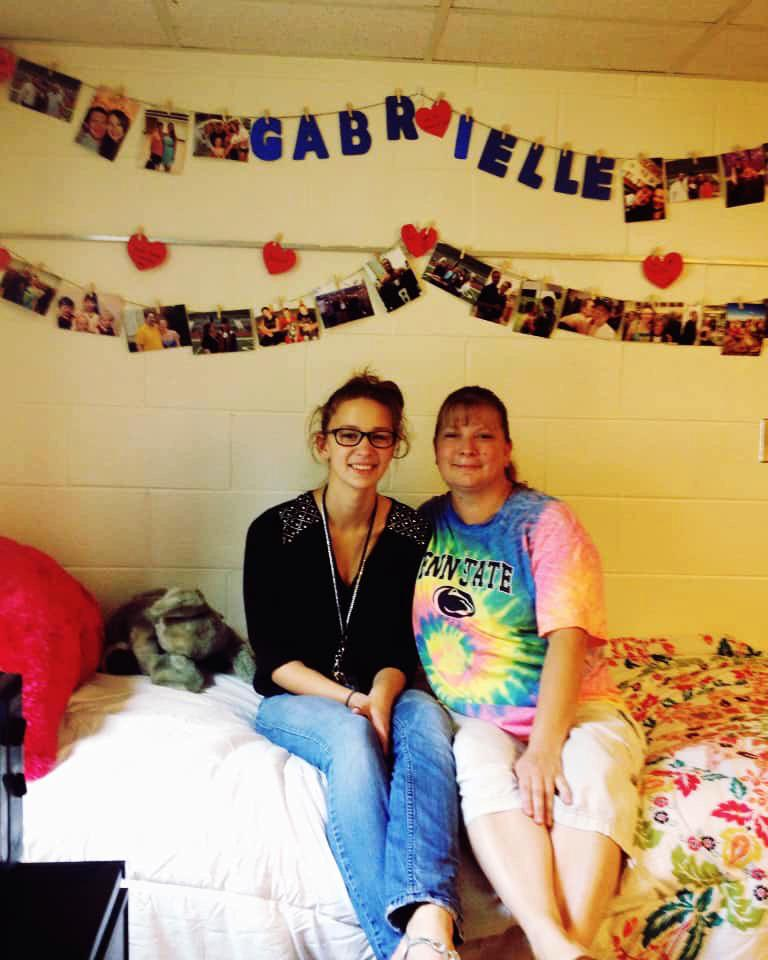 Gabrielle Davidson sits with her mother on the bed in her residence hall room.