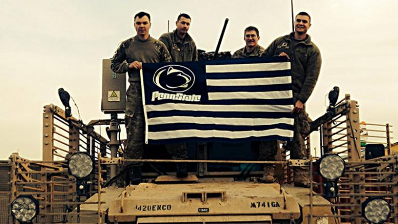 From left to right, Johnathan Bucher(Alumni), Joshua Keele, Christian Cieslak, Shaun Aiken proudly display a Penn State flag while on tour in Afghanistan.