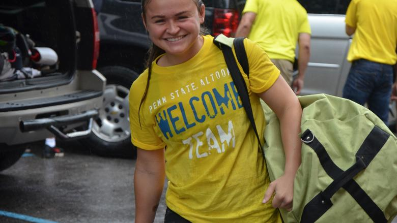 A student volunteer carries supplies to a first-year student's room