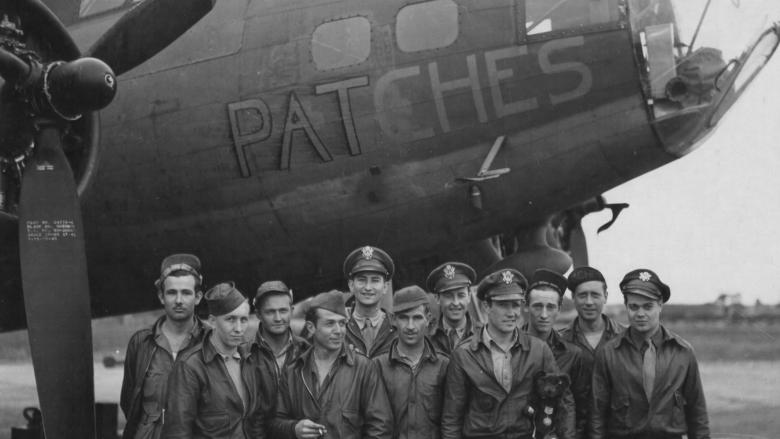 WWII flight crew stands in front of their plane in England