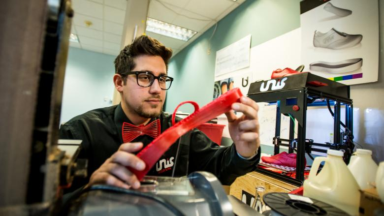 Nicholas Unis inspects a piece of his 3D-printed custom sneaker.