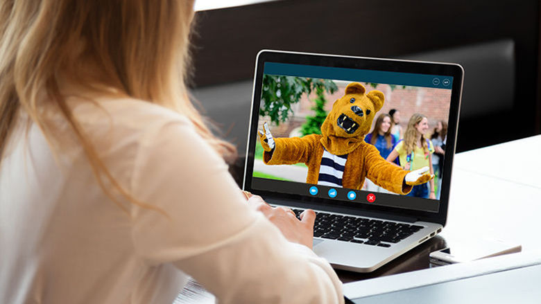 A woman chatting with the Nittany Lion on her laptop