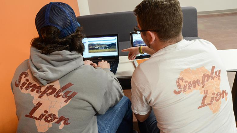 Logan McHale and Bill Butterfield working on their website and sporting their Simply Lion wear