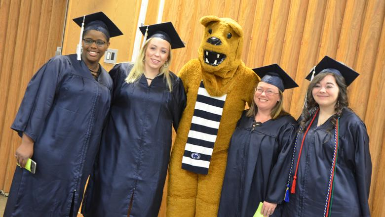 Graduates pose with the Nittany Lion at Fall 2017 Commencement ceremony.
