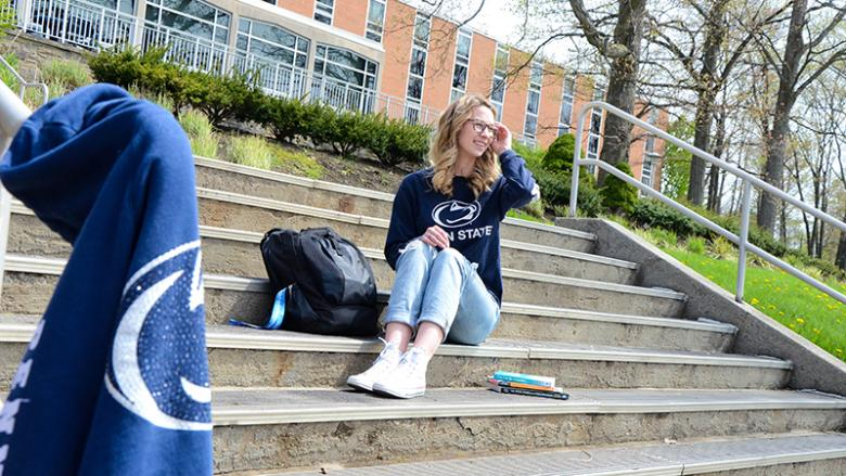 Gabrielle Davidson sits on the steps outside Oak Hall at Penn State Altoona