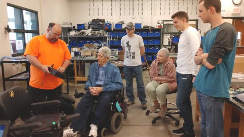 Brennecke and students demonstrate the automated wheelchair to Rich Harley