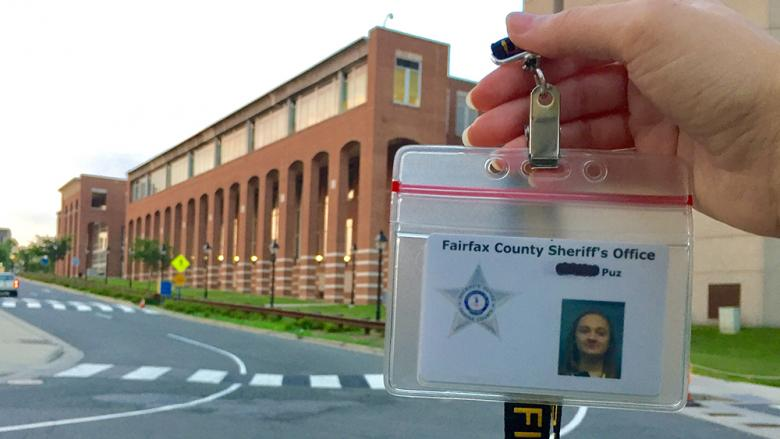 Alexis Puz displays her internship ID in front of the Fairfax County Sherrif's Office