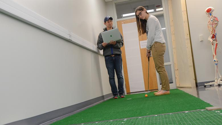 Takehiro Iwatsuki and kinesiology major Kierra Irwin work together on Iwatsuki's research regarding motor skills.