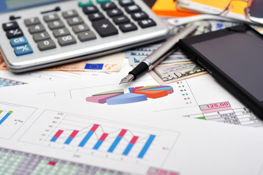 Accounting stock photo including charts, calculator, pen, and mobile phone