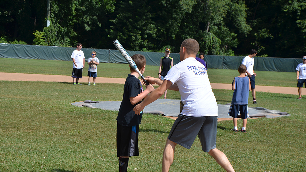 Students assist children in a game of baseball as part of the Voluntoona community service effort.